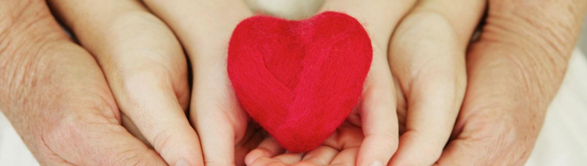Hender til personer fra tre generasjoner som holder et rødt hjerte